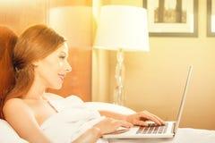 Kvinna som lägger i säng som kopplar av genom att använda att arbeta på bärbar datordatoren arkivfoton