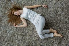 Kvinna som lägger på mattan Arkivbilder