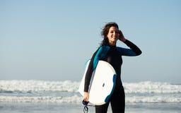 Kvinna som lämnar med bodyboard, når att ha surfat Arkivfoton