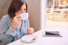 Kvinna som läppjar cappaccino i ett ljust kafé med minnestavlan Arkivfoto