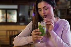 Kvinna som läppjar på en drink Arkivfoton