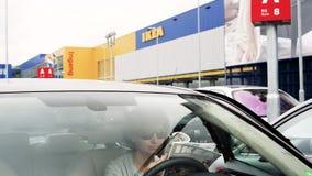 Kvinna som läser den IKEA katalogen inom bilparkering arkivfilmer