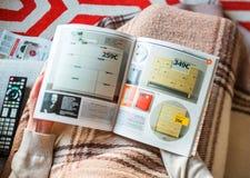 Kvinna som läser den IKEA katalogen som väljer den kabineda byrån arkivfoto