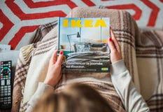 Kvinna som läser den IKEA katalogräkningen, innan att möblera huset arkivfoton