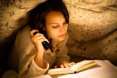 Kvinna som läser en bok arkivfoto