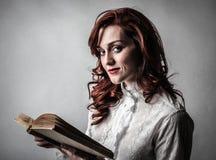 Kvinna som läser en bok Fotografering för Bildbyråer