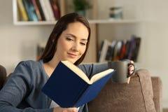 Kvinna som läser en bok som hemma kopplar av arkivfoto
