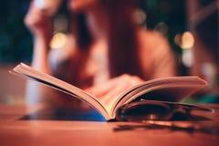 Kvinna som läser en bok i kafé Arkivfoton
