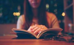 Kvinna som läser en bok i kafé Fotografering för Bildbyråer