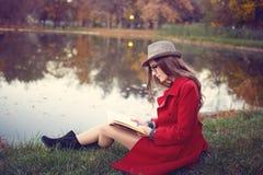Kvinna som läser en bok i parkera Royaltyfri Foto