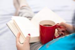 Kvinna som läser en bok i säng Arkivbilder