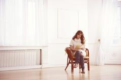 Kvinna som läser en bok i stol Arkivfoto