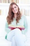 Kvinna som läser en bok, medan sitta på en vit soffa i en uppehälle arkivfoton