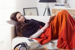 Kvinna som läser en bok som ner ligger på en soffa arkivbild