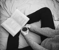 Kvinna som läser en bok och dricker kaffe i säng Arkivfoto
