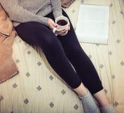 Kvinna som läser en bok och dricker kaffe i säng Arkivfoton