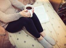 Kvinna som läser en bok och dricker kaffe i säng royaltyfria foton