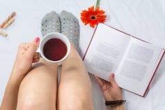 Kvinna som läser en bok och har kopp te arkivfoto
