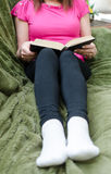 Kvinna som läser en bok på en soffa Arkivfoton