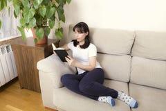 Kvinna som läser en bok på en soffa royaltyfri bild