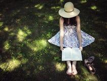 Kvinna som läser en bok utanför på gräset Royaltyfria Foton