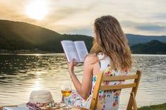 Kvinna som läser en bok vid sjön arkivbilder