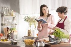 Kvinna som läser en kokbok royaltyfri foto