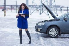 Kvinna som läser en manuellt bil och anseende nära hennes brutna bil Royaltyfria Foton