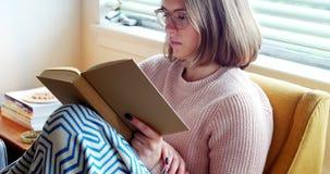 Kvinna som läser en roman i vardagsrum arkivfilmer