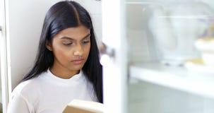 Kvinna som läser en roman i vardagsrum stock video