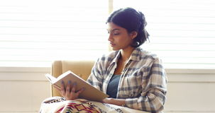 Kvinna som läser en roman i vardagsrum lager videofilmer