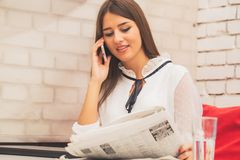 Kvinna som läser en tidning och talar på mobiltelefonen royaltyfri bild