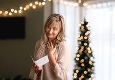 Kvinna som läser en uppriktigt meddelandeanmärkning eller kort royaltyfri fotografi
