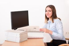 Kvinna som läser ett dokument i kontoret Arkivfoto