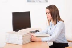 Kvinna som läser ett dokument i kontoret Arkivfoton