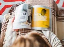 Kvinna som läser möblemang för kök för IKEA katalogköpande arkivbild