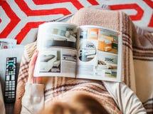 Kvinna som läser möblemang för sovrum för IKEA katalogköpande arkivfoto