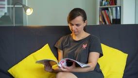 Kvinna som läser tidskriften lager videofilmer