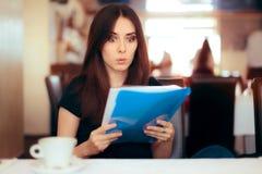 Kvinna som läser viktiga dokument i en restaurang Royaltyfria Foton