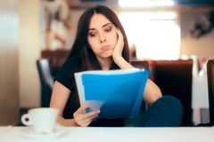 Kvinna som läser viktiga dokument i en restaurang Arkivbild