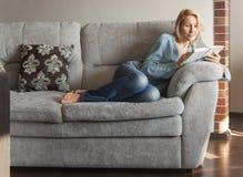 Kvinna som l?ser en bok p? soffan arkivfoto