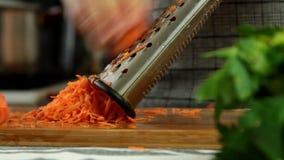Kvinna som lagar mat hemmastadda gradera morötter lager videofilmer