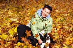 Kvinna som leker med henne hunden i höstpark Royaltyfria Foton