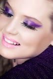 Kvinna som ler med purpur ögonskugga Fotografering för Bildbyråer