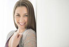 Kvinna som ler, medan luta på väggen hemma royaltyfri foto