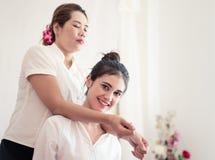 Kvinna som ler, medan ta thailändsk massage på hennes skuldra royaltyfri bild