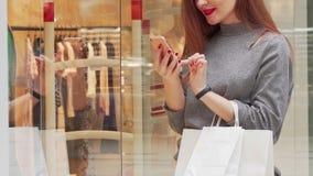 Kvinna som ler och att bläddra på hennes smarta telefon, medan shoppa på gallerian stock video