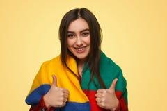Kvinna som ler och gör en gest tumme-UPS Arkivbilder