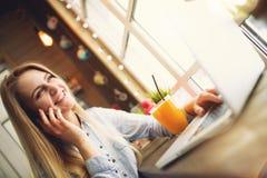 Kvinna som ler och talar med någon på telefonen som kopplar av i ett moderiktigt kafé som sitter på en tabell med en bärbar dator Royaltyfri Bild