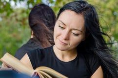 Kvinna som ler, som hon läser en boka Arkivfoto